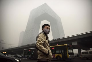 Image: A Chinese man wears a mask as he waits to cross the road