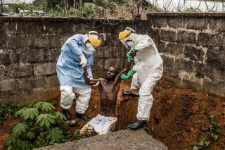 Image: Medical staff at the Hastings Ebola Treatment Center work to escort a man in the throes of Ebola-induced delirium
