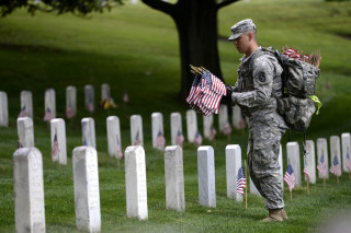 Image: The Old Guard places an American flag at headstones in Arlington National Cemetery