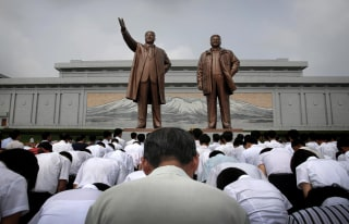 Image: North Koreans bow in front of bronze statues of the late leaders Kim Il Sung and Kim Jong Il