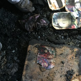 Image: Burned family pictures sit on the ground of a home in Duma, West Bank