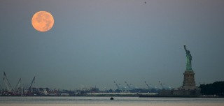 Image: A full moon, known as the Blue Moon, is seen over the Staten Island Ferry while it makes its way to New York