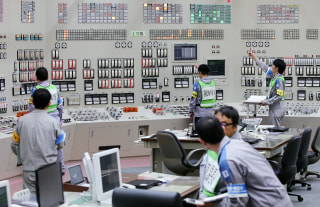 Image: Operators restart the nuclear reactor at the central control room of the Kyushu Electric Power Sendai nuclear power plant