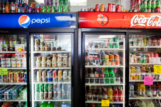 Image: Cans of soda are displayed in a case at Kwik Stops Liquor in San Diego