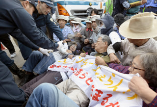 Image: Protesters lie on the ground as they try to block work on a contentious U.S. air base