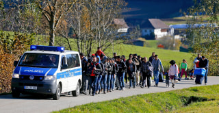 Image: Migrants are escorted by German police to a registration center