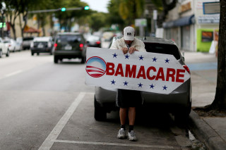 Image: Pedro Rojas holds a sign directing people to an insurance company where they can sign up for the Affordable Care Act