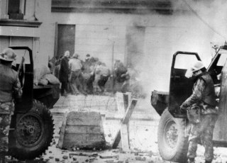 Image: Soldiers take cover behind armored vehicles in Londonderry, Northern Ireland, on Jan. 30, 1972