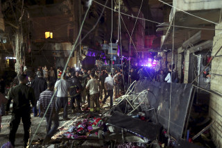 Image: Residents inspect a damaged area caused by two explosions in Beirut's southern suburbs, Lebanon