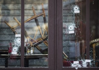 Image: Bullet holes are seen in the terrace windows of Cafe Bonne Biere