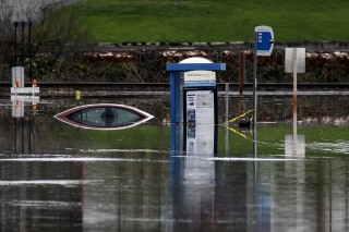 Image: A bus stop and a car sit in the flooded waters of the Stillaguamish River in Stanwood, Washington