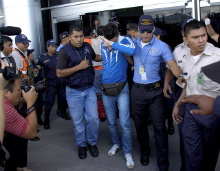 Image: Policemen escort one of five Syrian men detained at Toncontin international airport in Tegucigalpa