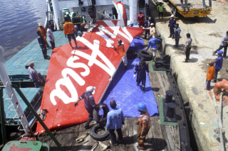Image: File photo of a section of AirAsia flight QZ8501's tail being loaded onto a boat