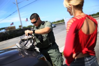 Image: Broward Sheriff's Office Sergeant Ozzy Tianga checks a woman's purse to see if she is carrying flakka