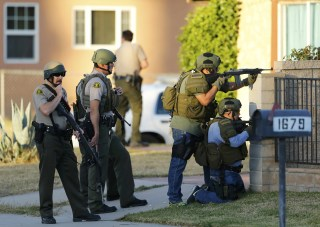 Image: Police officers conduct a manhunt after a mass shooting in San Bernardino