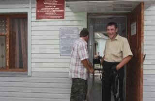 Image: Patients stand near a building of the Novokhopersky Neuropsychiatric Home in the village of Alferovka in the Voronezh region, Russia