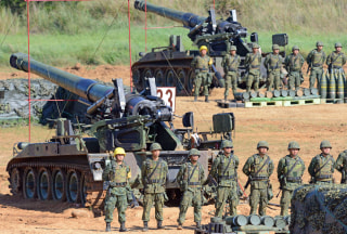 Image: Taiwan military soldiers stand guard next to a 155-millimeter howitzer