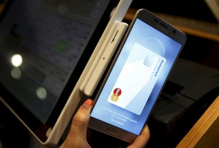 Image: File photo of an employee demonstrating a Samsung Pay, Samsung's new mobile payment system at a shop in Seoul