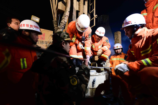 Image: Rescuers try to contact the trapped people at a collapsed mine