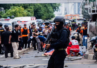 Image:A policeman stands guard in front of the blast site