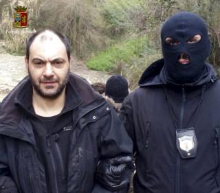 Image: A police officer escorts fugitive Giuseppe Ferraro