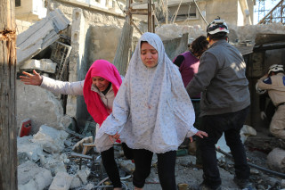 Image: Girls react following a reported Syrian regime air strike in Aleppo on Monday.