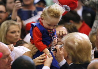 Image: Republican U.S. presidential candidate Donald Trump signs the arm of 19-month-old Curtis Ray Jeffery II after a rally in Baton Rouge, Louisiana