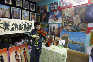 Image: An orphan boy plays music at the Iraqi Safe House for Creativity in Baghdad