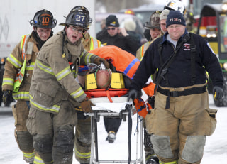 Image: Emergency personnel carry someone away from a crash scene near Fredericksburg, Pa.