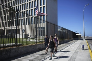 Image: Tourists pass by the U.S. Embassy in Havana