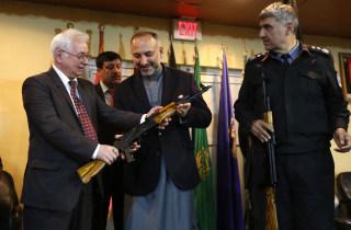 Image: Russia's Ambassador to Kabul Alexander Mantytskiy hands an AK-47 to Afghan National Security Adviser Mohammad Hanif Atmar