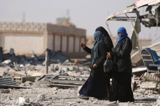 Image: Women walk on rubble in al-Shadadi town, in Hasaka province