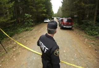 Image: Mason County Sheriff's Chief Criminal Deputy Russ Osterhout looks down a road