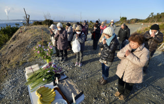 Image: People pray toward the sea to mourn victims of the March 11, 2011 earthquake and tsunami disaster in Fukushima prefecture