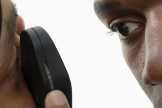 GP using ophthalmoscope to examine young mans eye