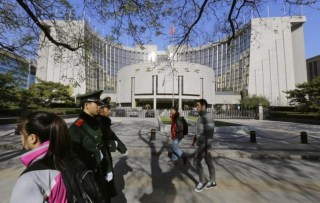 People walk past PBOC headquarters in Beijing