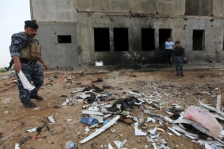 Image: Iraqi security forces inspect the aftermath of a suicide bombing at a soccer field in Iskandariya