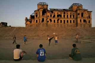 Image: Afghan men play soccer in front of the bombed out old royal palace, in Kabul, Afghanistan, Wednesday, Sept. 23, 2009. The palace was designed by a French architect and originally built in 1923 by King Amanullah.