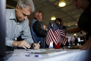 A job seeker fills out papers at a military job fair in San Francisco