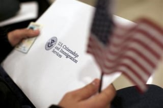 A man holds a U.S. flag while receiving his proof of U.S. citizenship during a ceremony in San Francisco