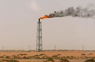 A gas flame is seen in the desert near the Khurais oilfield