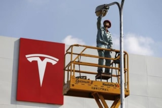 A labourer repairs street lamp next to logo of Tesla Motors in front of new showroom of the company in Shanghai