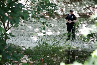 Image: An officer stands watch in the bed of Waller Creek on the University of Texas campus in Austin