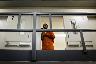 An inmate watches from his cell as DC Mayor Muriel Bowser tours DC Central Jail after announcing policy changes to support employment for inmates during and after incarceration in Washington