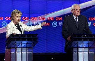 Image: Democratic U.S. presidential candidate Clinton gestures towards rival candidate Sanders as she speaks during a Democratic debate in New York