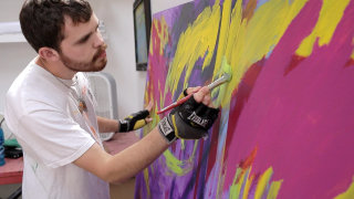 Image: Autistic artist Jeremy Sicile-Kira works on a painting at his San Diego studio.