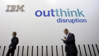 People walk past an IBM logo during the Mobile World Congress in Barcelona