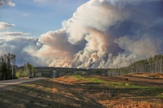 Image: Smoke billows from the Fort McMurray wildfires as a truck drives down the highway in Kinosis