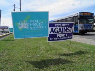 Campaign signs concerning a municipal vote over fingerprint requirements for ride-hailing companies such as Uber and Lyft are seen along a roadway in Austin