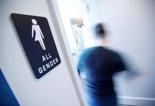 Image: A bathroom sign welcomes both genders at the Cacao Cinnamon coffee shop in Durham, North Carolina
